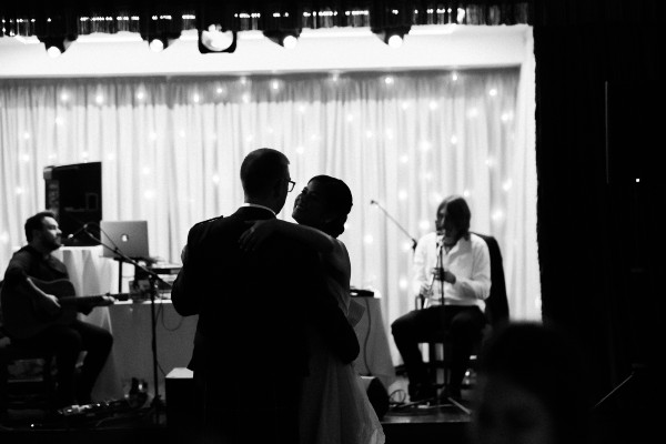 Black and white photo of wedding couple dancing with musicians at the back