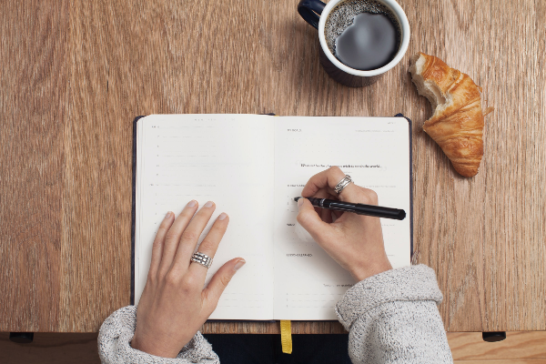 Writing a list on a notebook, coffee and half eaten croissant